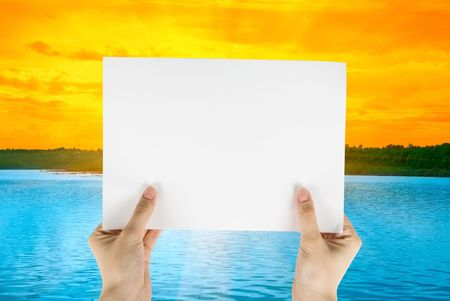 Hand holding white paper at beauty sunset on river background photo