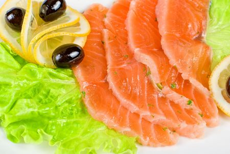 Salmon closeup with lettuce, lemon and olive on white background photo