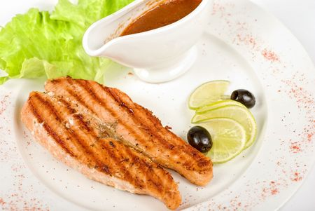 Grilled trout steak with sauce,greens, lemon and olive photo