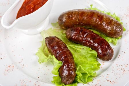 grilled sausage closeup with lettuce and red sauce photo