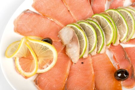 Sliced chum salmon and mackerel decorated with limes, lemons and olives photo