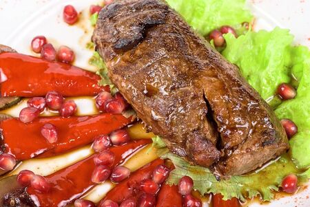 Roasted beef steak with pomegranate closeup at plate Stock Photo - 6740780