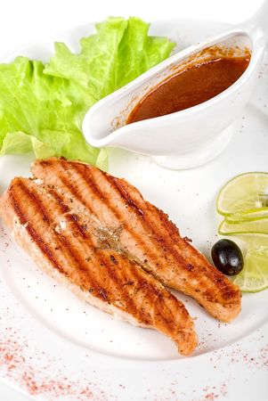 Grilled trout steak with sauce,greens, lemon and olive Stock Photo - 6740798