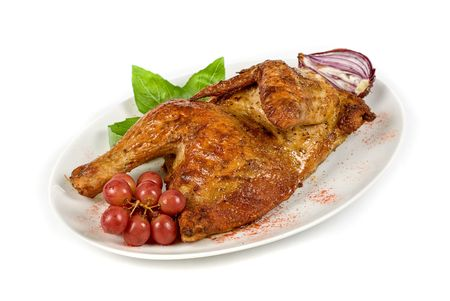 Half grilled chicken closeup with grape and greens on a white photo