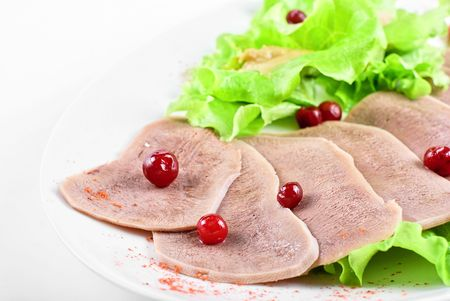 Beef tongue with cranberry closeup with green lettuce and mustard photo