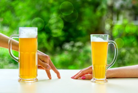 two hands, man and woman with beer in glass photo