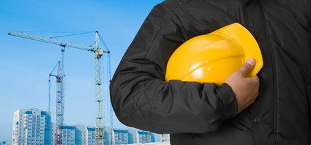 Closeup of builder with yellow helmet on building panorama background Stock Photo - 6962976