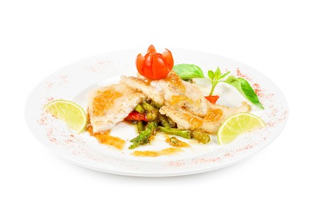 Roast halibut filet with vegetables on a white photo