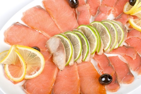 Sliced chum salmon and mackerel closeup decorated with limes, lemons and olives photo