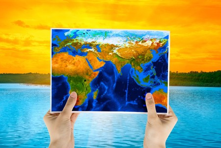 Hand holding map at beauty sunset on Lake, and orange sky photo