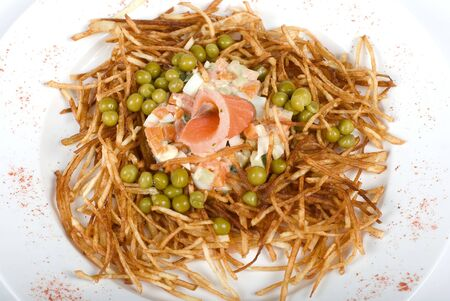 Closeup of salad with salmon fish at fried sliced potato with carrot and peas dressed by tomato sauce with cognac photo