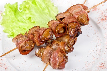 Kebab from chicken liver wrapped with bacon and garlic sauce photo
