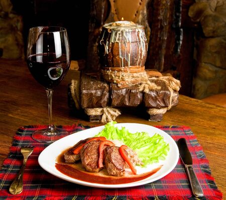 Roast maral meat with blood and garnish pearl barley at table with wine photo