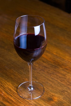 red wine glass over at wooden table background photo