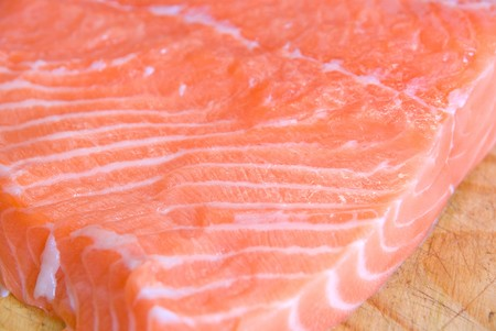 salmon closeup slice at wooden board photo