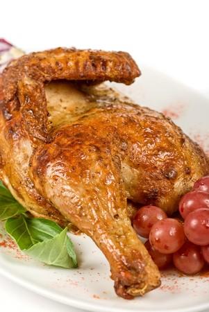 half and half: Mitad a la parrilla portarretrato de pollo con uva y verdes sobre un blanco Foto de archivo