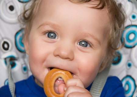 pretty baby boy laughing portrait with bread ring photo