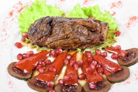 Roasted beef steak with pomegranate closeup at plate Stock Photo - 7096998