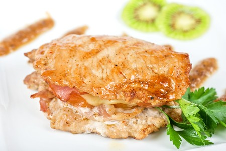 Cooked pork chop on a white plate with kiwi and parsley Stock Photo - 7096913