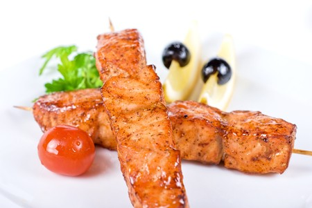 salmon kebab at plate with green lettuce and lemon on a white Stock Photo - 7096857