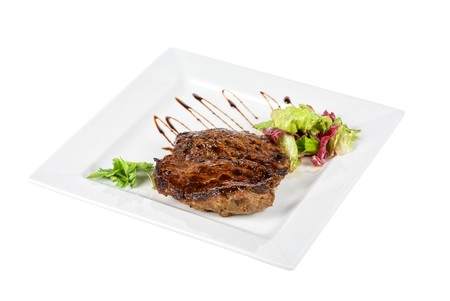Beef steak on a white plate with vegetables on a white