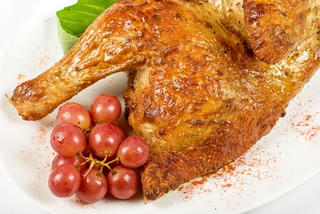 Half roasted chicken closeup with grape and greens on a white photo