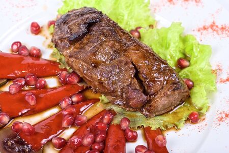 Roasted beef steak with pomegranate closeup at plate photo