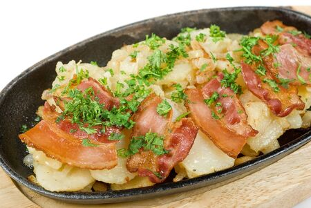 Fried potato with bacon and vegetables on a white photo