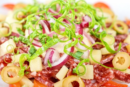 closeup of salad from salami, vegetables and olives photo