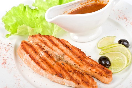 Grilled salmon steak with sauce,greens, lemon and olive photo