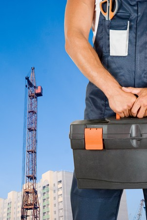 repairman with box of instruments on building background Stock Photo - 7208467