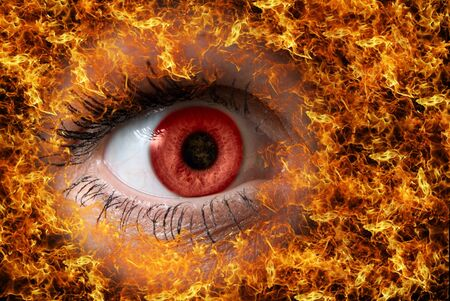 light brown eyes: extreme close-up of red female eye on fire