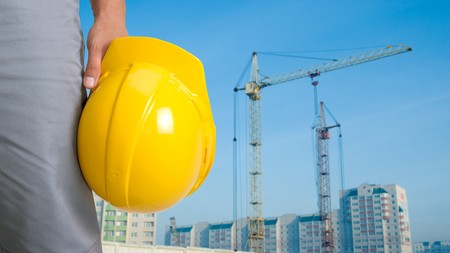 work clothes: Closeup of builder with yellow helmet on building panorama background