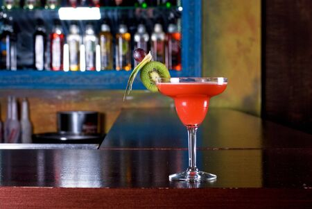 red cocktail with kiwi on the wooden bar