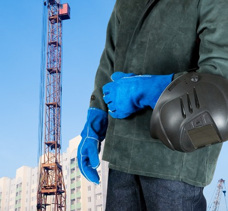 male welder closeup with welding equipment on building background photo