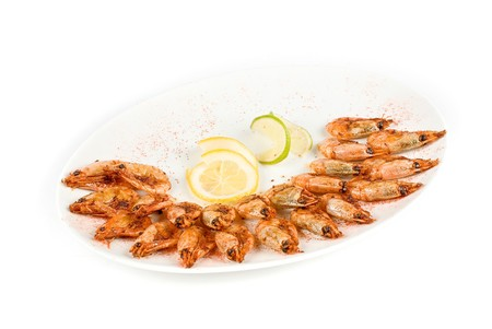 roasted shrimps with lemon closeup isolated on a white background photo