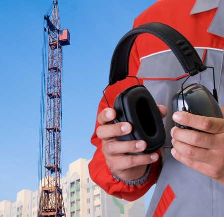 protective headphone at man hands on building background Banque d'images