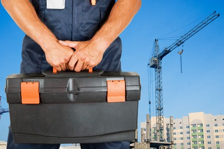meter box: repairman with box of instruments on building background Stock Photo