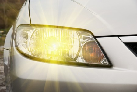 Car headlight of silver automobile closeup
