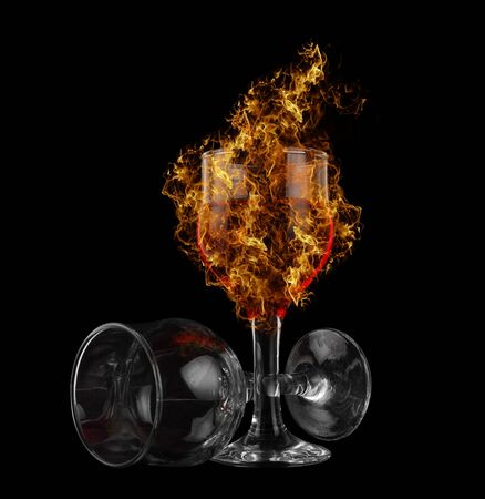 half full: red wine at fire on black background Stock Photo