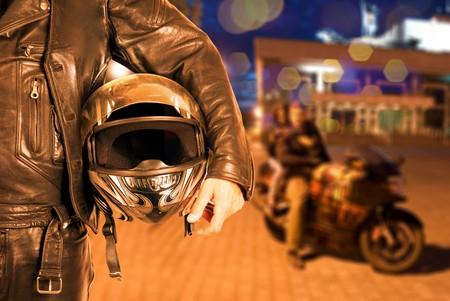 motociclista: Portarretrato de motociclista en el fondo de la ciudad de noche