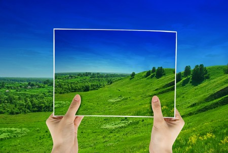 photo of green field in hands on nature background photo