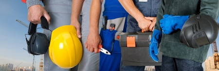 home safety: workers closeup with equipment on building background