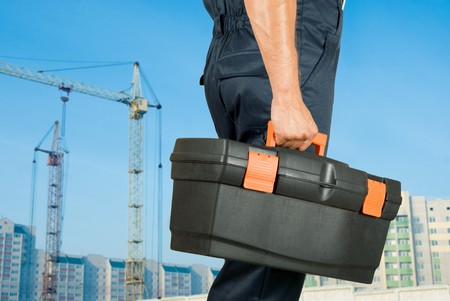 repairman with box of instruments on building background Banque d'images