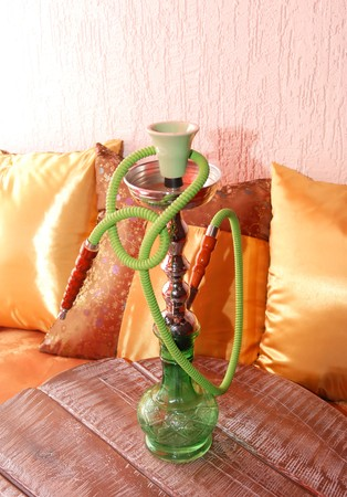 Green hookah over yellow pillows and decorations photo