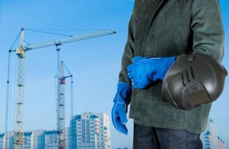 male welder closeup with welding equipment on building background Banque d'images