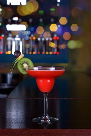 red cocktail with kiwi on the wooden bar photo