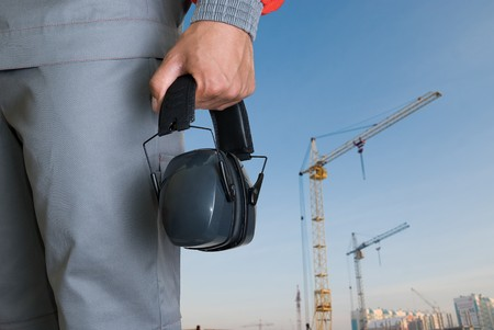 protective headphone at man hands on building background photo