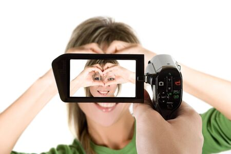 Lovely blond girl with hands as heart at camcorder photo