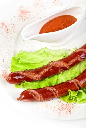 grilled sausage closeup with lettuce and sauce isolated on white photo